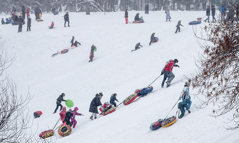 People sliding down a slope during a snowfall.