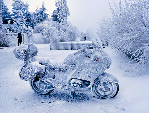 A BMW motorbike is covered with snow and ice as it is parked on top of the Feldberg mountain near Frankfurt, January 29