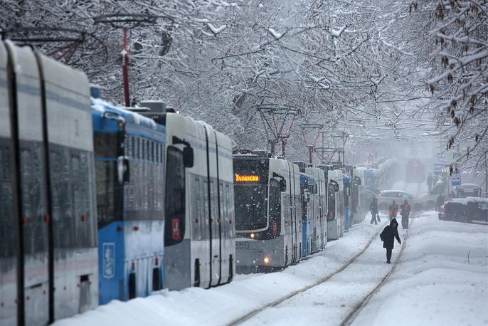 Trams are seen during a snowfall near Shchukinskaya metro station