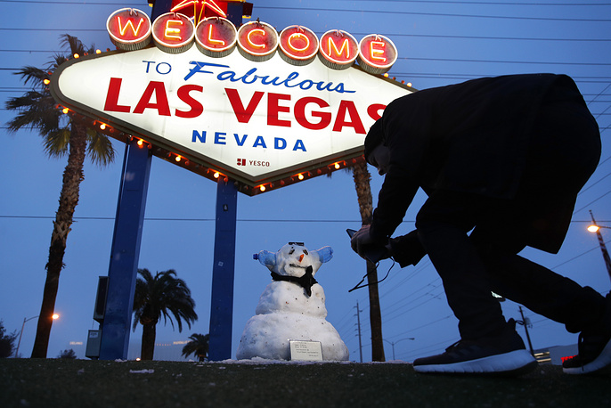 """A man takes a picture of a small snowman at the """"Welcome to Fabulous Las Vegas"""" sign along the Las Vegas Strip, Las Vegas, February 21. Las Vegas is getting a rare taste of real winter weather, with significant snowfall across the metro area in the first event of its kind since record keeping started back in 1937"""