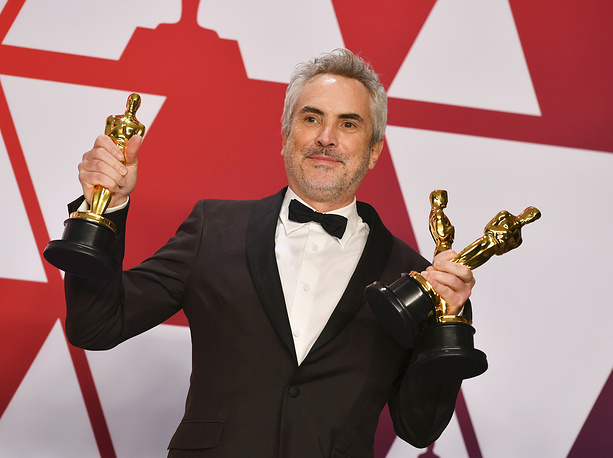 "Alfonso Cuaron poses with the awards for best director for ""Roma"", best foreign language film for ""Roma"", and best cinematography for ""Roma"" in the press room at the Oscars in Los Angeles"
