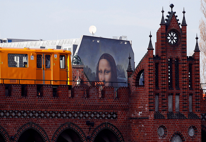 """A U-Bahn underground train passes by a mural by Berlin-based street art gang """"Die Dixons"""" (The Dixons) which features a giant reproduction of Leonardo da Vinci's artwork Mona Lisa, near East Side Gallery, Berlin, February 25"""