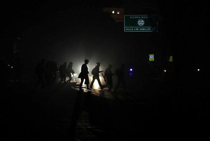 People walk in a street in the dark during a power outage in Caracas