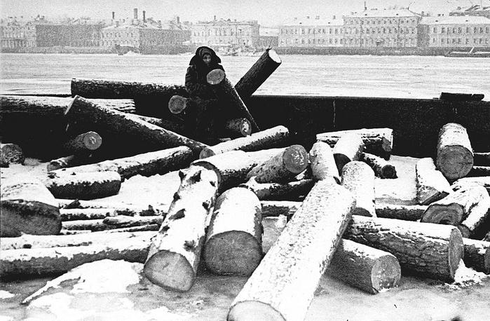 Женщина на ленинградской набережной у штабеля дров в одну из блокадных зим.