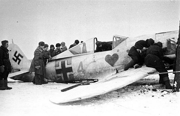 Советские военнослужащие осматривают немецкий самолет Фокке-Вульф Fw 190, сбитый под Ленинградом.Изображение сердца под кабиной пилота — знаменитое «Зеленое сердце» («Grünherz»), эмблема 54-й истребительной эскадры.