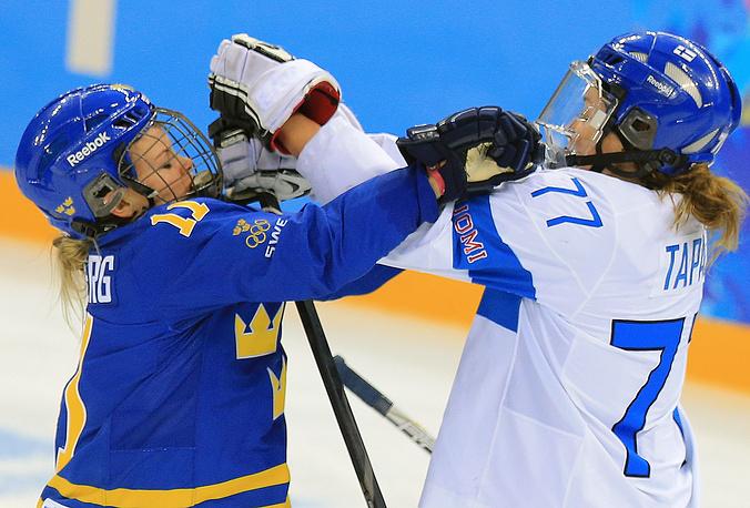 Игроки сборной Швеции Сесилия Остберг и сборной Финляндии Сюзанна Тапани (слева направо) в матче 1/4 финала по хоккею среди женщин: Финляндия - Швеция