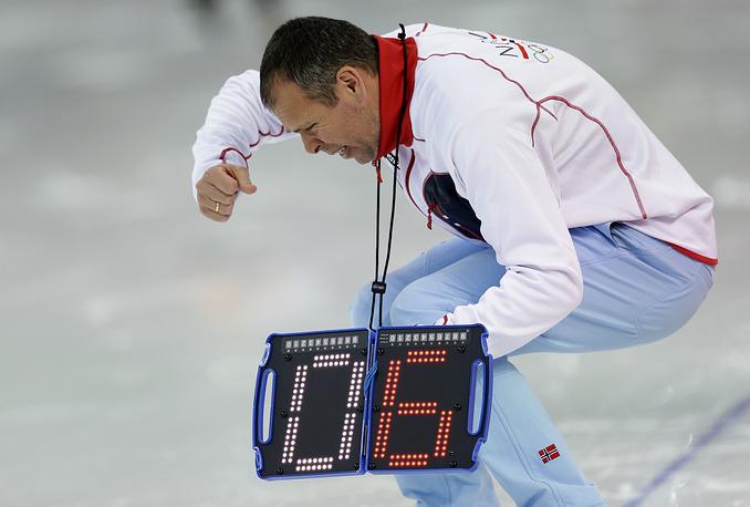Норвежский тренер реагирует на выступление своего спортсмена в беге на 1500 метров в соревнованиях по конькобежному спорту среди мужчин