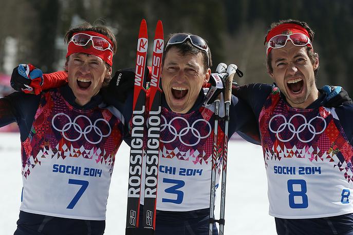 Российские спортсмены Максим Вылегжанин, занявший второе место, Александр Легков, занявший первое место, и Илья Черноусов, занявший третье место (слева направо) в масс-старте свободным стилем на дистанции 50 км