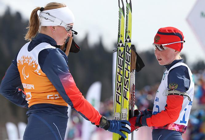 Россиянки Юлия Будалеева, завоевавшая серебряную медаль, и ведущая Татьяна Мальцева (справа налево) на финише гонки на короткой дистанции среди женщин с нарушением зрения в соревнованиях по биатлону