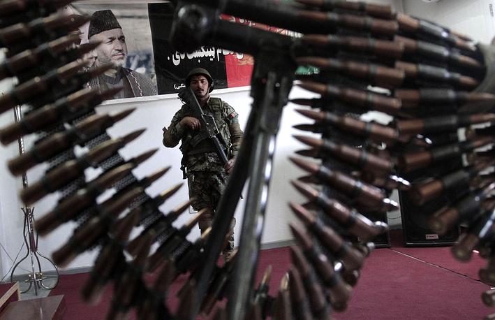 Карзай назвал два условия для подписания документа: прекращение авианалетов на дома мирных афганцев и помощь США в восстановлении мира в Афганистане. На фото: портрет Карзая и коллекция оружия и боеприпасов, захваченных афганской армией, Кабул, 2013 год