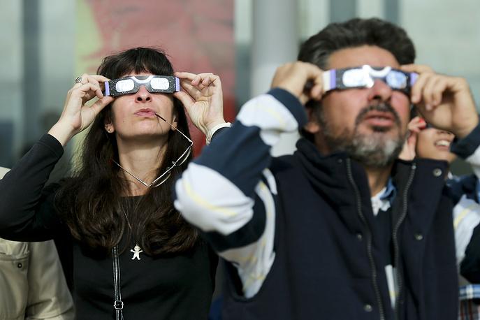 Люди в защитных очках наблюдают солнечное затмение в Эшториле, Португалия, 2013 год