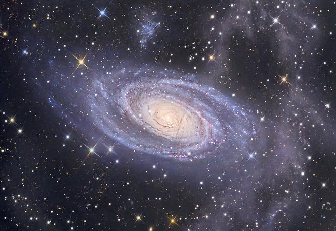 Спиральная галактика М81 в созвездии Большой Медведицы - одна из самых ярких на нашем небе. Она расположена на расстоянии 11,8 млн световых лет от Земли и по размеру сопоставима с Млечным Путем. Над галактикой виден ее спутник - карликовая галактика Холмберг IX