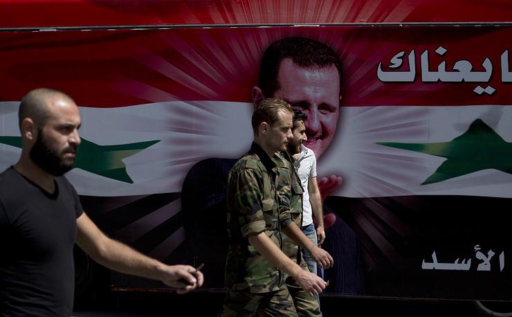 Сирийские солдаты на фоне автобуса с портретом Башара Асада