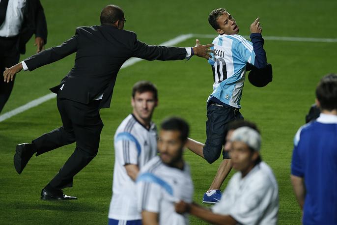 Охранник пытается поймать фаната, выбежавшего на поле