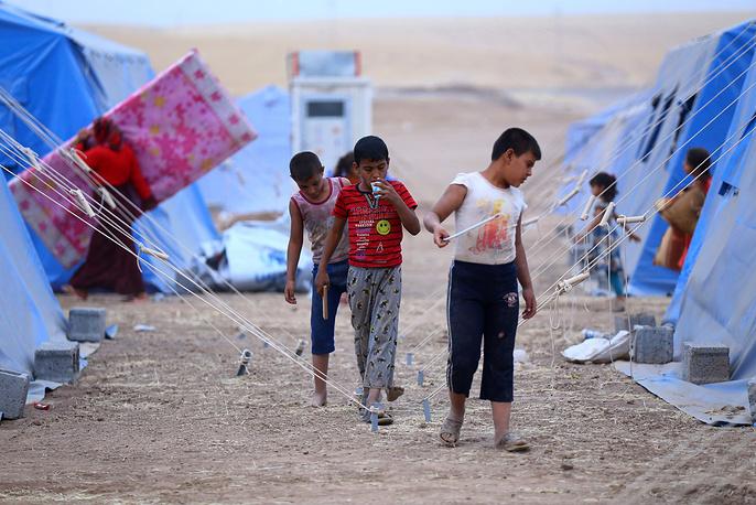 Дети в лагере для беженцев недалеко от города Эрбиль на севере Ирака. Сотни тысяч людей покинули свои дома в Мосуле после нападения боевиков