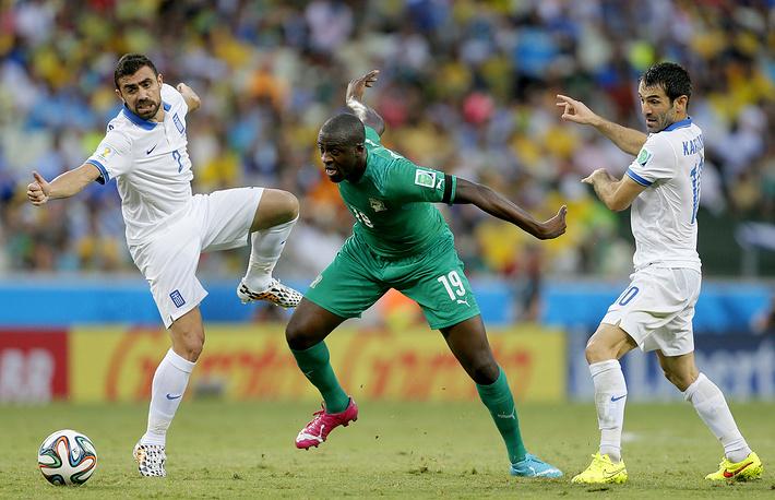Ивуарийский полузащитник Яя Туре в борьбе с греческими игроками