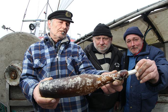 """Шотландский моряк отправил свое послание в специальной экспериментальной бутылке, предназначенной как раз для морской почты. В 1890 году в Британии была выпущена ограниченная партия подобных """"конвертов"""". В открытке было указано, что человека, вернувшего отправителю содержимое бутылки, ждет награда в шесть пенсов. На фото: немецкие рыбаки с бутылкой, внутри которой была открытка, отправленная в 1913 году"""