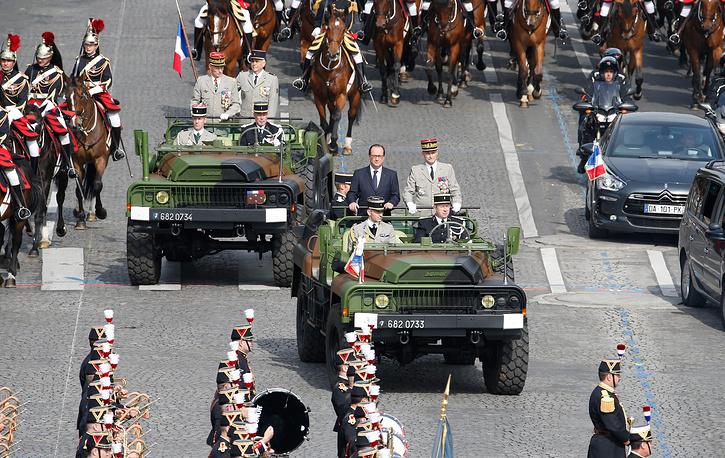 Президент Франции Франсуа Олланд (в центре) и начальник штаба французской армии генерал Пьер де Вилье (справа) прибывают на площадь Согласия в сопровождении Республиканской конной гвардии