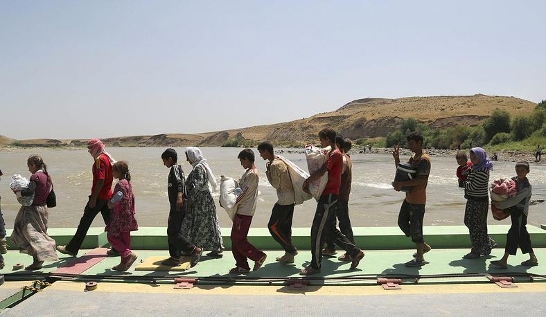 """Боевики суннитской экстремистской организации """"Исламское государство"""" (ИГ) заявили о захвате около 15 населенных пунктов на севере Ирака. На фото: иракские езиды пересекают сирийско-иракскую границу"""