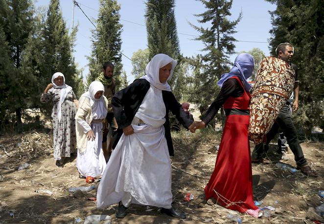 Из региона были вынуждены бежать десятки тысяч человек, большинство из них представители религиозных меньшинств - христиане и езиды. На фото: езиды пересекают сирийско-иракскую границу