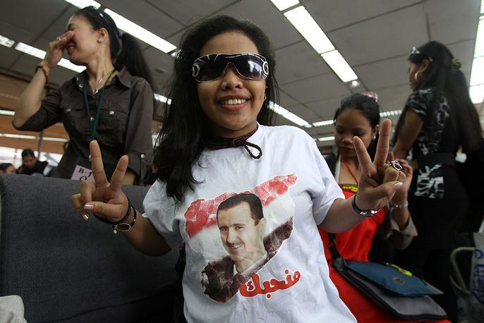 Филиппинка, вернувшаяся на родину из Сирии, в футболке с портретом президента Сирии Башара Асада, 2012 год