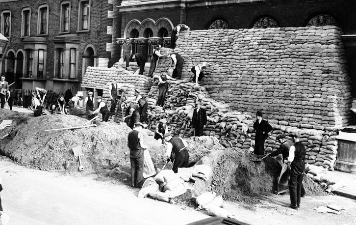 Рабочие наполняют мешки песком и складывают из них стенки для защиты зданий в Лондоне от бомбардировок. 5 сентября 1939 года