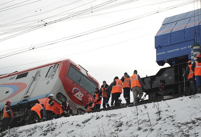 Рабочие на месте столкновения поезда и локомотива