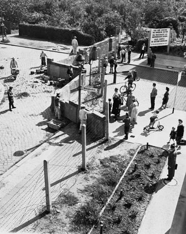 В ночь на 13 августа 1961 года силами Национальной народной армии ГДР были установлены временные заграждения, а 18 августа началось возведение бетонной стены. На фото: западные берлинцы (справа) наблюдают за тем, как рабочие Восточного Берлина возводят стену на улицах Вильденбрухштрассе и Хайдельбергерштрассе, август 1961 года