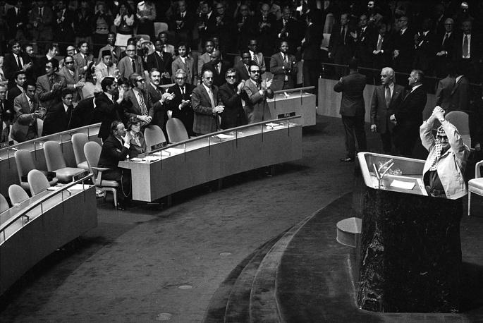 """В 1974 году принята новая программа Организации освобождения Палестины, предусматривающая переход от исключительно террористических методов борьбы к стратегии, включающей политические шаги, в том числе возможность признания Израиля. На фото: 13 ноября 1974 года Ясир Арафат впервые выступает на заседании Генассамблеи ООН: """"Я пришел к вам с оливковой ветвью в одной руке и оружием борца за свободу в другой. Не дайте оливковой ветви выпасть из моей руки"""""""