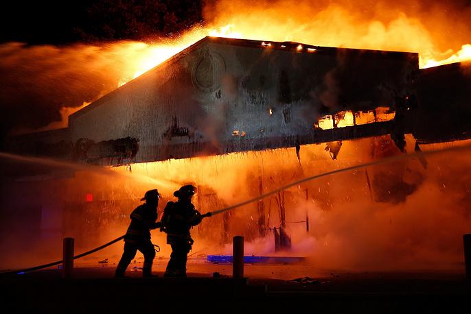 """Участники акции протеста подожгли несколько зданий. В частности, огонь охватил склады, магазин автозапчастей и салон красоты. На фото: пожарные тушат горящее здание ресторана """"Маленький Цезарь"""" в Фергюсоне"""