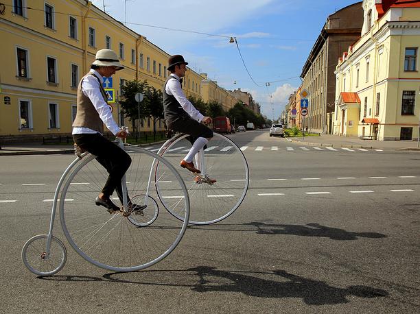 """19 июля. Участники твидовой велопрогулки """"Пять мостов"""" в центре Санкт-Петербурга. Ежегодно на велопробег собираются до 1 тыс. человек. В этом году темой прогулки стал Париж 1940-х годов. Самый первый твидовый велопробег был проведен в январе 2009 года в Лондоне"""