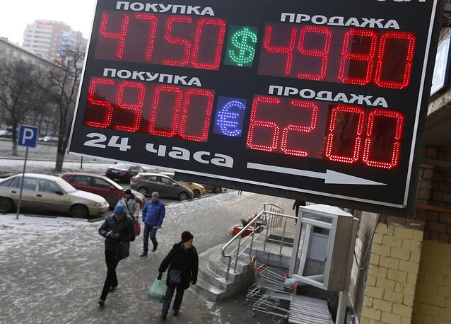 В начале торгов в пятницу на Московской бирже рубль снизился до 49,47 руб./$. Курс евро к рублю при открытии достигал 62,03 руб. На фото: электронное табло у пункта обмена валют, 28 ноября