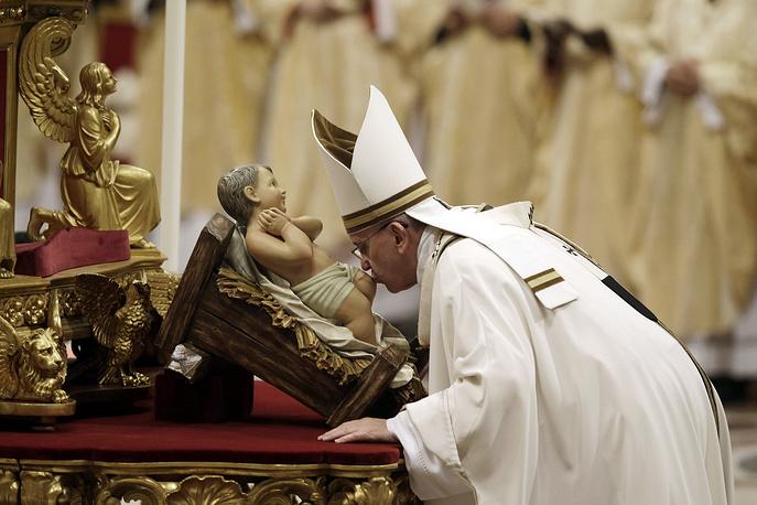 Папа римский Франциск целует статую младенца Иисуса во время мессы в канун Рождества в базилике Святого Петра в Ватикане, 24 декабря