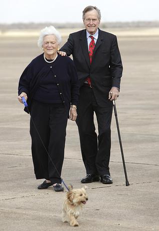 Бывший президент США Джордж Буш-старший и Барбара Буш выгуливают своего питомца, 2009 год
