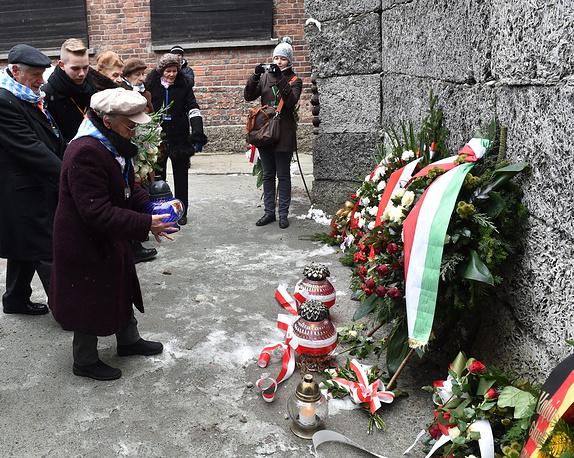 Бывшие заключенные лагеря возлагают цветы к так называемой стене смерти в рамках мероприятий в память о жертвах холокоста в Освенциме, Польша