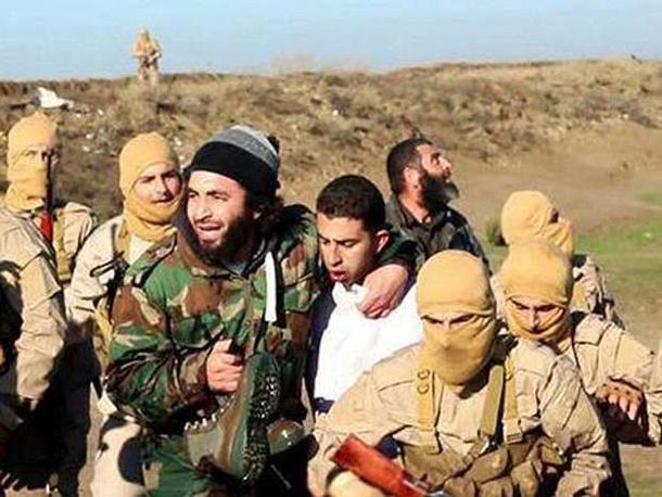"""Боевики """"Исламского государства"""" позируют с захваченным в плен пилотом иорданских ВВС Муазом Юсефом Аль-Касасба"""