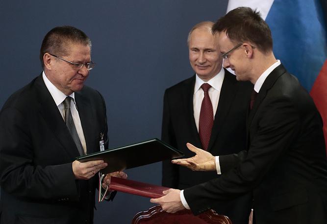Министр экономического развития РФ Алексей Улюкаев и президент России Владимир Путин (слева направо) на церемонии подписания совместных документов