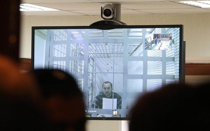 1 апреля суд отменил арест трех фигурантов дела об убийстве Бориса Немцова - Шадида Губашева, Тамерлана Эскерханова и Хамзата Бахаева. Между тем главный обвиняемый Заур Дадаев, арест которого признан законным, вновь отказался от своих показаний. На фото: Хамзат Бахаев (на экране) во время рассмотрения жалобы на арест в Мосгорсуде