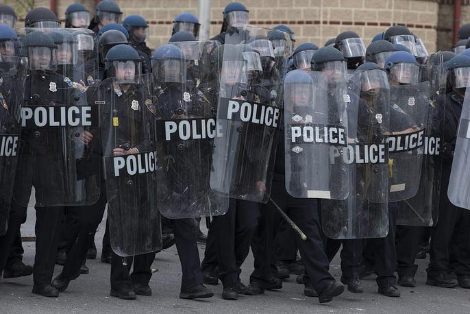 """25 апреля около 2 тыс. демонстрантов прошли по улицам Балтимора с плакатами """"Полицейских-убийц - в тюрьму!"""" и почтили минутой молчания память Грэя, остановившись возле госпиталя, где он умер. Затем они провели митинг на площади перед мэрией. Некоторые демонстранты выкрикивали угрозы в адрес полицейских, следивших за порядком во время шествия, и бросали в их сторону пустые пластиковые бутылки. На фото: акция протеста против действий полиции в Балтиморе"""