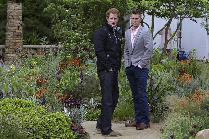 Британский принц Гарри осматривает экспозицию курируемого им благотворительного фонда Sentebale, которая посвящена проблеме бедственного положения детей в Лесото. Сад создан ландшафтным дизайнером Мэттом Кейтли (на фото справа)