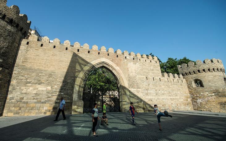 Дети играют в футбол у стены в исторической части города