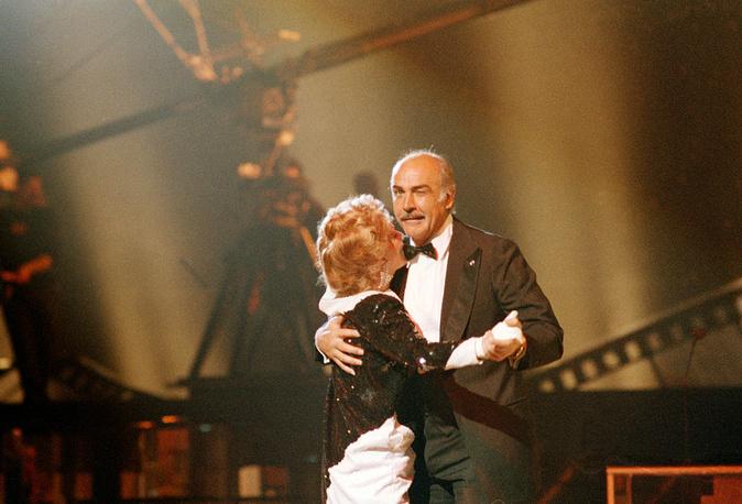 """Коннери танцует с актрисой Жанной Моро на церемонии вручения премии """"Сезар"""" в Париже, 1987 год"""