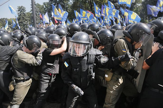 Из толпы протестующих неизвестный бросил в милицейское оцепление вокруг здания парламента боевую гранату