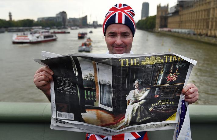 Мужчина читает специальный выпуск газеты The Times, который посвящен королеве Елизавете II как самому долгоправящему монарху Великобритании, 9 сентября