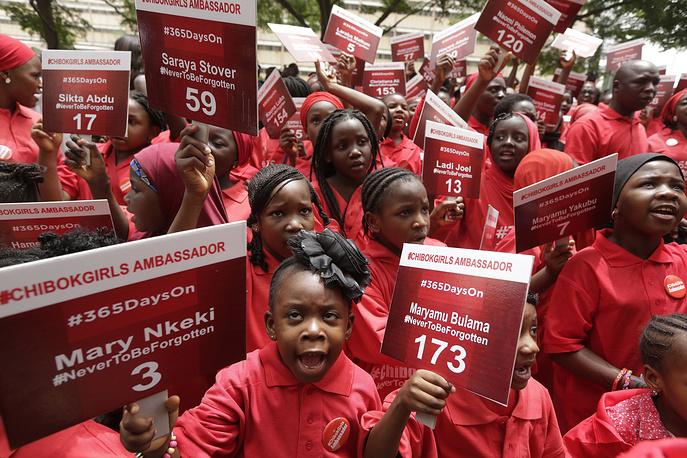 """Насилие в отношении девочек распространено во всех странах. Список стран, где девочки в возрасте 10-14 лет наиболее часто подвергаются телесным наказаниям, возглавляют Йемен, Египет, Нигерия, Чад и ЦАР. На фото: девушки несут плакаты с именами девочек, похищенных из школы в Нигерии боевиками """"Боко Харам"""", выступающими против """"западного образования"""", Нигерия, 2015 год"""