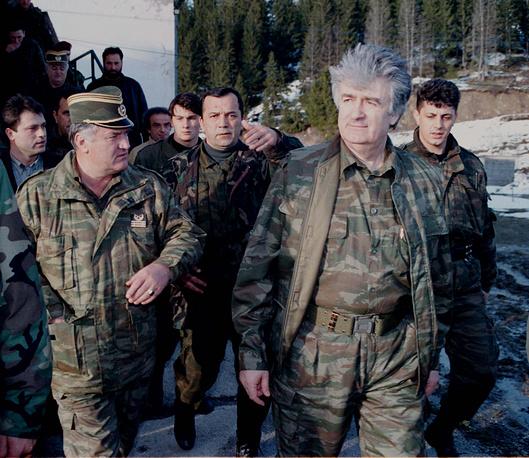 Караджич (второй справа) и генерал Ратко Младич (первый слева) в сопровождении телохранителей на горе Власич на линии фронта в Сербии 15 апреля 1995 года. Младичу также предъявлено обвинение в геноциде, нарушении законов и обычаев войны, преступлениях против человечности