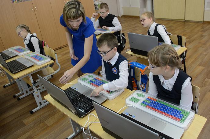 Ученики на уроке русского языка с использованием ноутбуков и клавиатур для людей с нарушенной координацией движений
