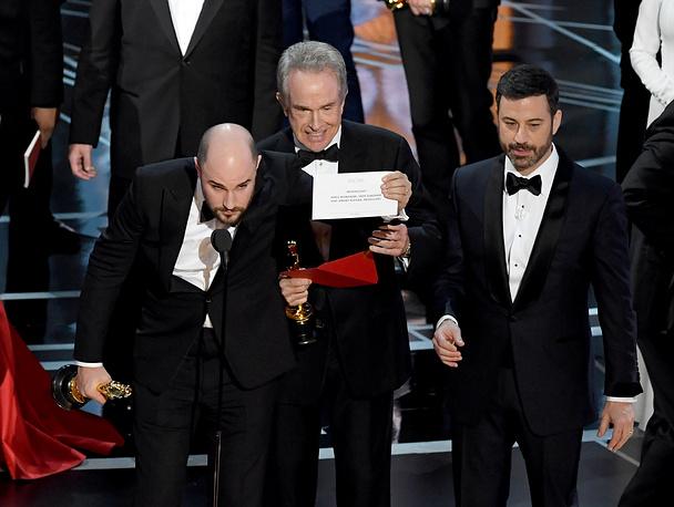 """Продюсер мюзикла """"Ла-ла Ленд"""" Джордан Хоровиц держит карточку с названием картины, победившей в номинации """"Лучший фильм"""" — """"Лунный свет"""". Рядом с продюсером  (слева направо) актер Уоррен Битти и ведущий 89-й церемонии """"Оскар"""" Джимми Киммел"""