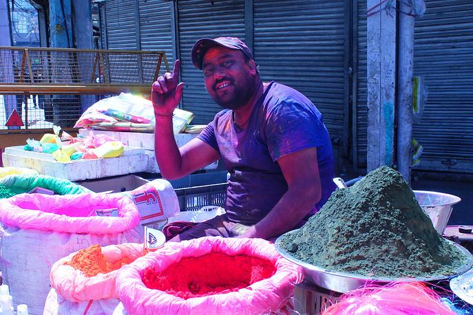 Торговцы красками и цветными порошками сидят прямо на улице, продажа идет на вес из мешков, в каких на этой же улице в обычные дни торгуют специями