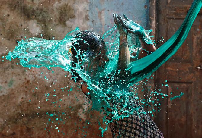 Девушку обливают раскрашенной водой на фестивале в Мумбаи